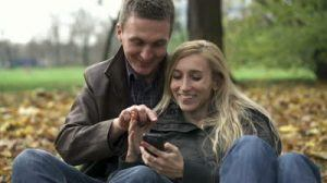 stock-footage-happy-couple-with-smartphone-in-autumn-park