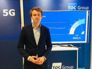 TDC Groups koncernstrategidirektør Lasse Pilgaardstår foran fartmåleren, der viser de høje hastigheder fra 5G-testen. (foto: TDC)